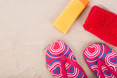 Flipflops ,sunscreen,towel on sand beach — 图库照片