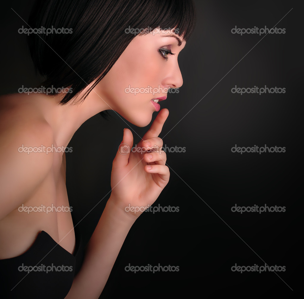 Beautiful Young Woman touching her  lips  on a black background — Stock Photo #11537713