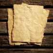 Old paper on wooden wall — Stock Photo