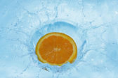 Orange splashing in water — Stock Photo