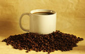 Hot cup of coffee on a pile of coffee beans — Stock Photo