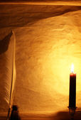 Paper, quill, & ink lit by candle — Stock Photo