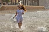Młoda kobieta szczęśliwa uruchomiony na plaży — Zdjęcie stockowe