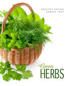 Green herbs in braided basket — Stock Photo