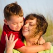 Portrait of happy mother and son hugging at beach with sand dunes in background — Stock Photo #10756076