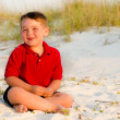 Portrait of happy child on beach with sand dunes in background — Stock Photo