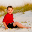 Portrait of happy child on beach with sand dunes in background — Stock Photo #10756095