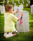 Child straightening a flag at veterans cemetery — Stock Photo