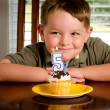 Young boy blowing out his birthday candle — Stock Photo