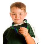 Happy child in soccer or football uniform with medal isolated on white — Stock Photo