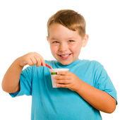 Young child eating yogurt isolated on white — Stock Photo