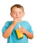 Happy child drinking orange juice — Stock Photo