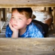 Stock Photo: Unhappy child hiding and sulking while playing on playground