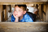 Unhappy child hiding and sulking while playing on playground — Stock Photo