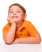 Happy attentive child sitting and listening at desk — Stock Photo