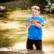 Child playing in mud in forest creek — Stock Photo