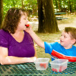 Mother and child having picnic at park under forest canopy of trees — Stockfoto