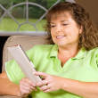 Woman reading book using an e-reader while relaxing at home — Stock Photo