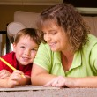 Mother helping child with writing lesson for school while at home — Stock Photo #11316923