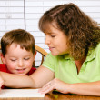 Mother helping child with writing lesson for school while at home — Foto de Stock
