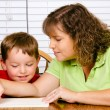 Mother helping child with writing lesson for school while at home — ストック写真