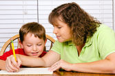 Mother helping child with writing lesson for school while at home — Stock Photo