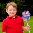 Child playing with American flag pinwheel to celebrate Independence Day on July Fourth — Stock Photo #11496456