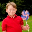 Child playing with American flag pinwheel to celebrate Independence Day on July Fourth — Stock Photo