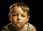 Portrait of serious, sad, angry or depressed child isolated on black — Stock Photo