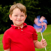 Child playing with American flag pinwheel to celebrate Independence Day on July Fourth — Stok fotoğraf