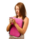 Texting teen schoolgirl reacts with shock and surprise isolated on white — Stock Photo