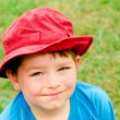 Child in summer portrait wearing bright red hat outdoors at park — ストック写真
