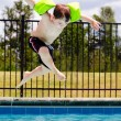 Foto Stock: Child jumping into pool while going on swimming outing during summer