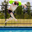 Child jumping into pool while going on swimming outing during summer — Foto Stock #11585790