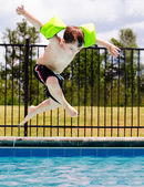 Child jumping into pool while going on swimming outing during summer — Foto Stock