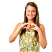 Smiling teenager girl making heart shape with her hands isolated on white — Stock Photo