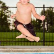 Child jumping into pool while going on swimming outing during summer — Foto Stock #11751726