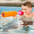 Child playing with water gun while swimming in pool during summer — Stock Photo #11751727