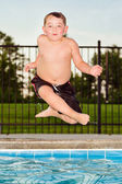 Child jumping into pool while going on swimming outing during summer — 图库照片