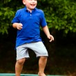 Child playing while jumping on trampoline — Stock Photo