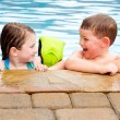 Children playing together laughing and smiling while swimming in pool — Stock Photo #11930047