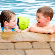 Stock Photo: Children playing together laughing and smiling while swimming in pool