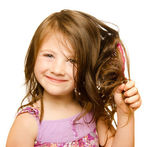 Hair care concept with portrait of girl brushing her unruly, tangled long hair isolated on white — Stock Photo