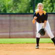 Teen girl playing softball in organized game - Stock Photo