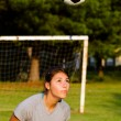 Stock Photo: Teen girl heading soccer ball while playing on field