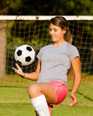 Teen girl juggling soccer ball with her knees — Stock Photo