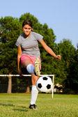 Teen girl kicking soccer ball on field — Stock Photo
