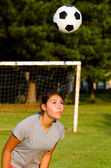 Teen girl heading soccer ball while playing on field — Stock Photo
