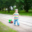 Baby boy running along the road with a toy car — Stock Photo