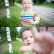 Stock Photo: Baby boy walking in park with funny face